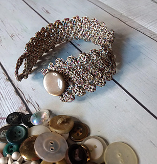 Delicate looking bronze crochet bracelet on a background of white-painted wood. Pile of buttons in the foreground.