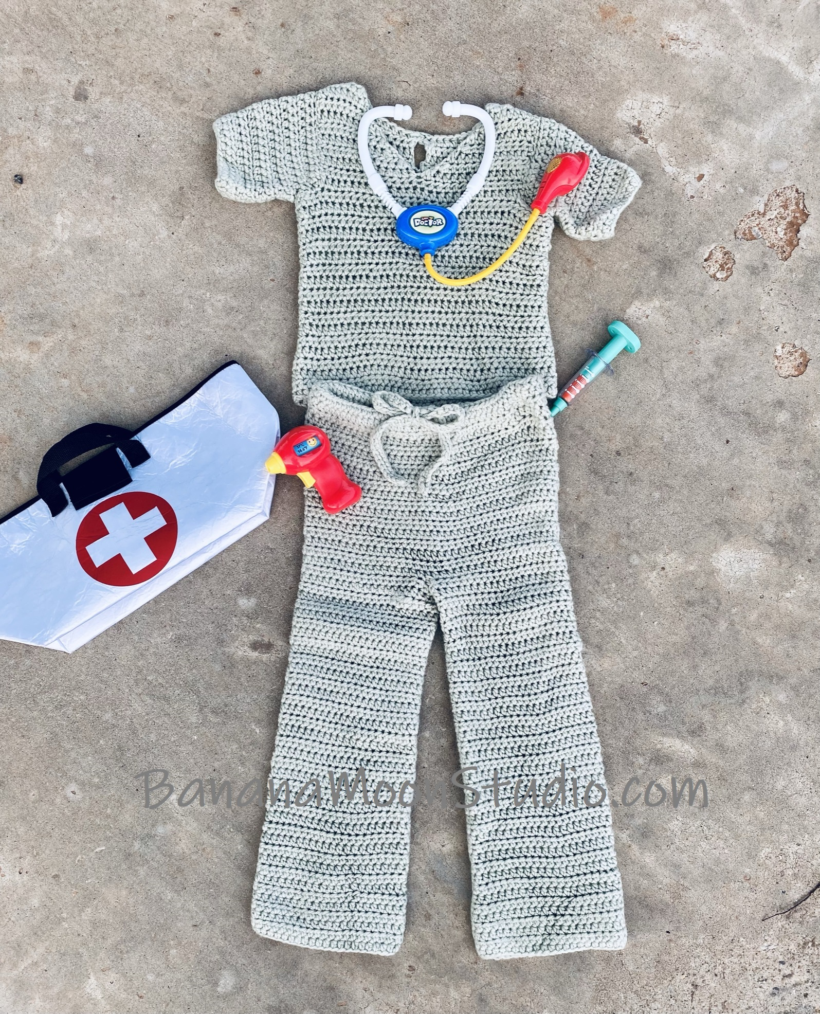Pale green crochet top and drawstring pants on a gray background. White bag with white and red cross, children's toy thermometer, syringe, and stethoscope. Text reads BananaMoonStudio.com.