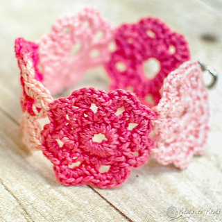 Crochet bracelet made of small flowers in two colors of pink. The bracelet sits on a wooden background.