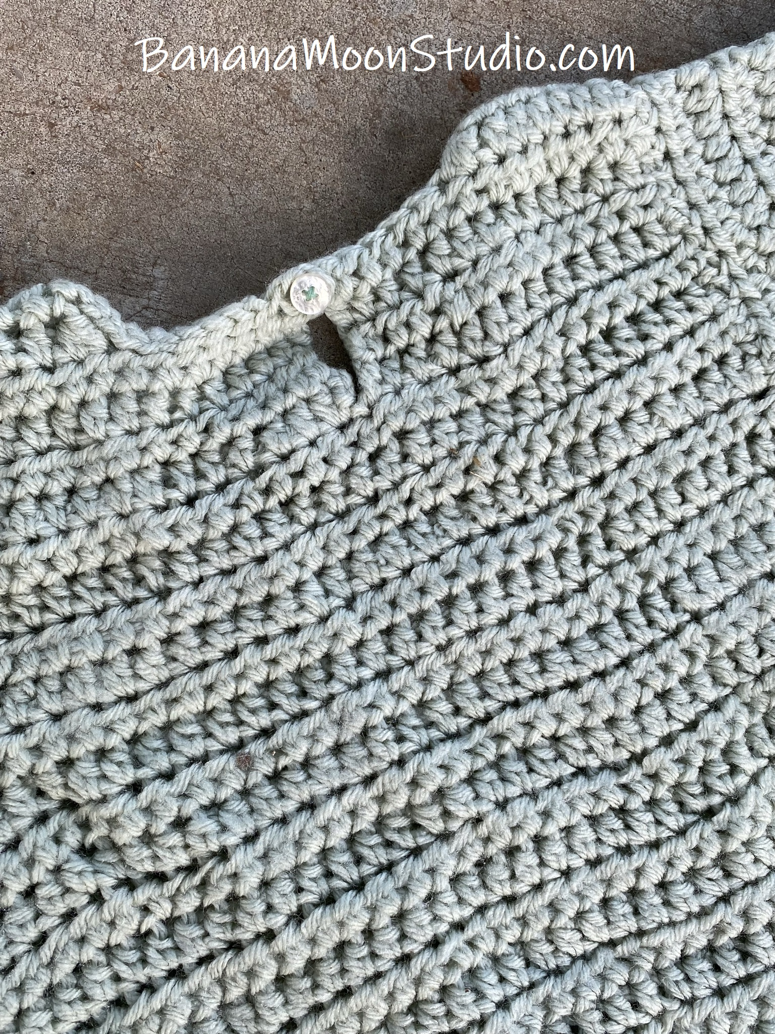 Back of a crochet top on a gray background.