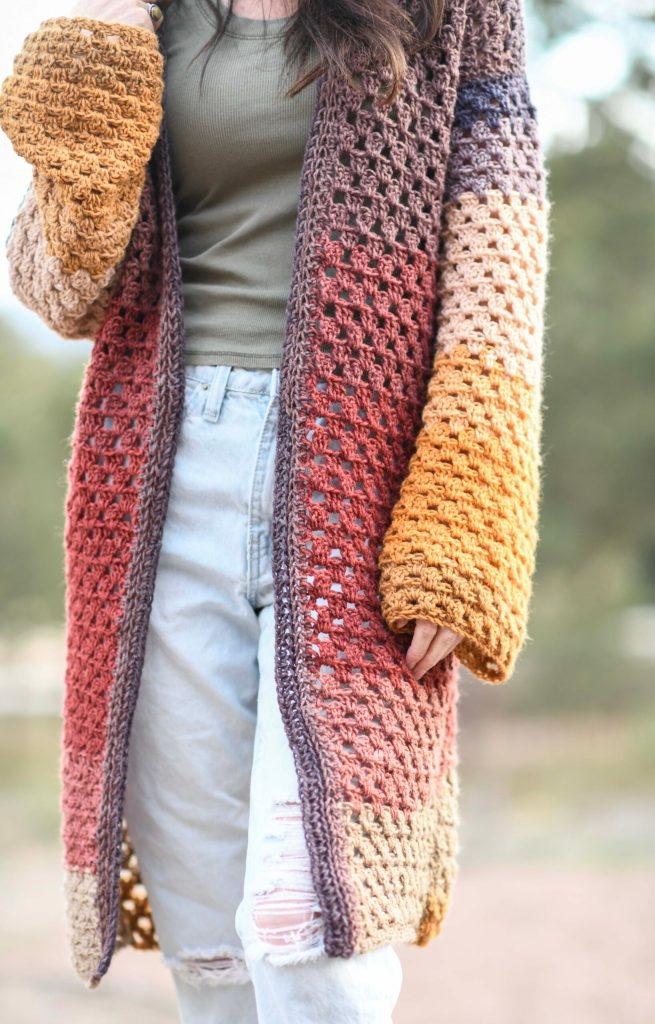 Woman wearing a knee-length crochet granny stitch cardigan with long sleeves. The cardigan changes colors from dusty purple at the top through melon, salmon, peach, and yellow.