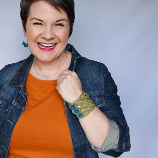Woman smiling at the camera, wearing earrrings, necklace, denim jacket, orange shirt, and a wide cuff bracelet that is crocheted. The bracelet is olive green and has three blue buttons.