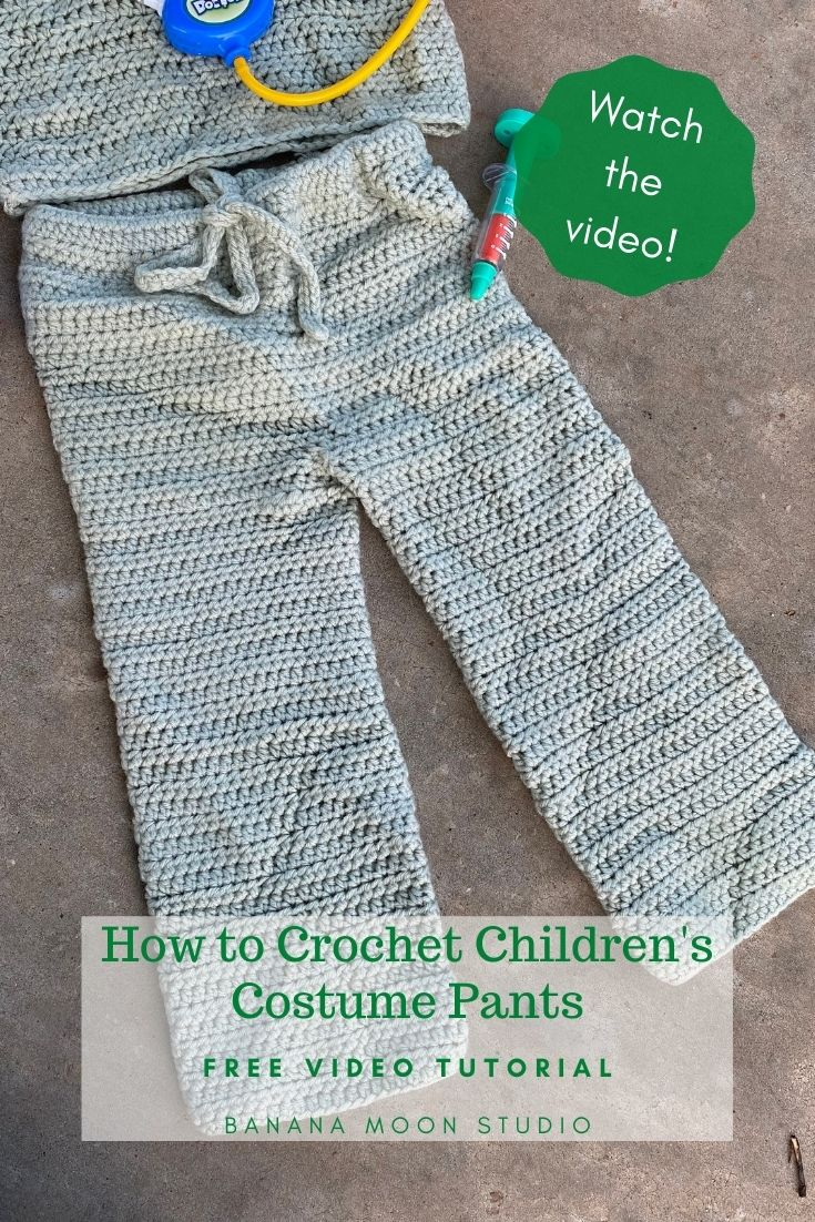 Crochet drawstring pants, pale green, on a brown background with kids doctor toys. Text reads: Watch the video! How to Crochet Children's Costume Pants. Free video tutorial. Banana Moon Studio.
