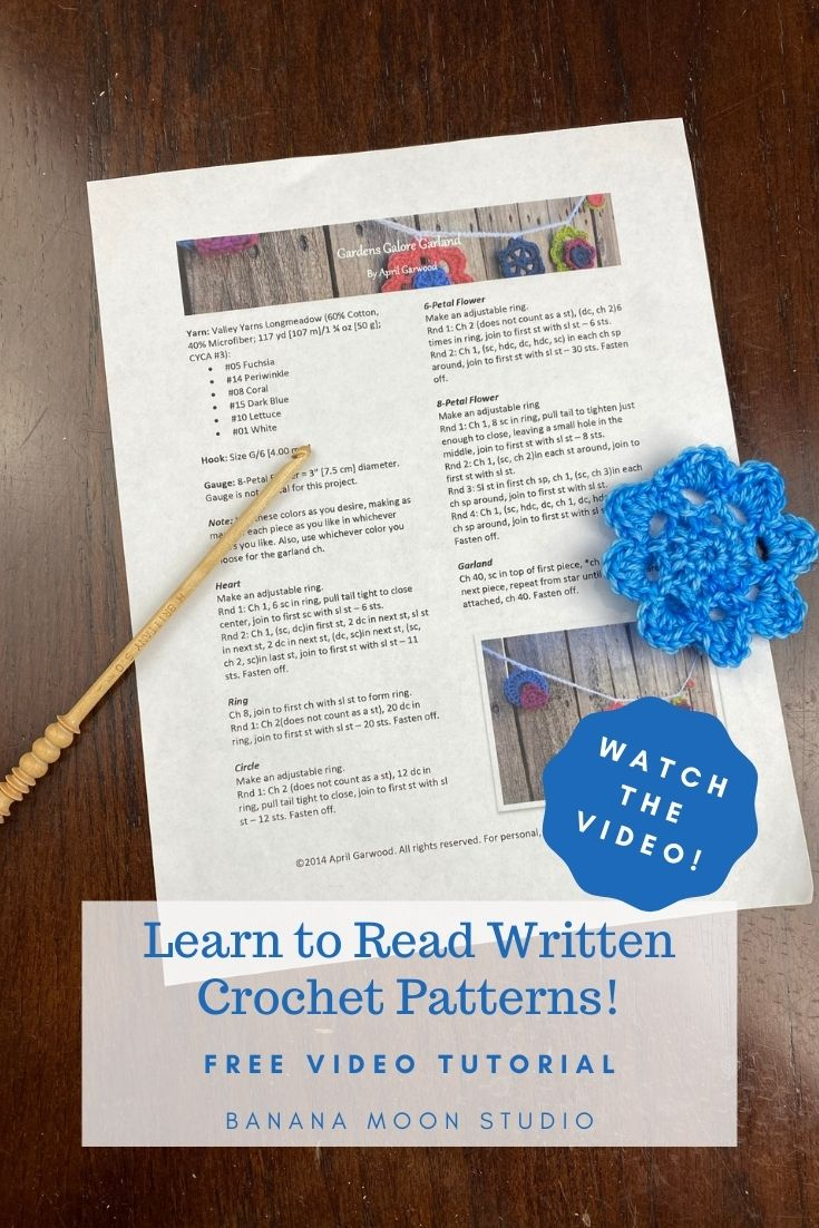 Written crochet pattern sitting on a table with a crochet hook and a blue crochet flower. Text reads: Watch the video! Learn to read written crochet patterns! Free video tutorial. Banana Moon Studio.