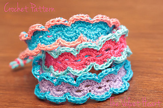 Three crochet bracelets sitting on a table. The bracelets are each made of bright colors of crochet thread in aqua and pale orange, watermelon and sea green, and pink and sky blue.