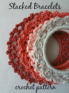 Four crochet bracelets sitting on a white background. Each bracelet looks to be crocheted around a store-bought bangle and works outward to make a lacy bracelet. Bracelets are white, pale coral, darker coral, and salmon. Text reads: Stacked Bracelets crochet pattern.