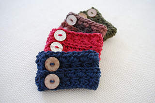 Four wide cuff bracelets are fanned out, slightly overlapping, on a white background. Each bracelet has two buttons. The cuffs are navy blue, red, brown, and green.