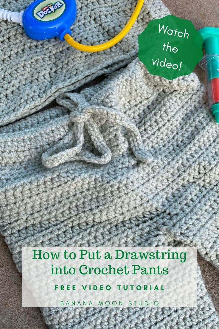 Crochet drawstring pants on a brown background with children's toys. Text reads: Watch the video! How to put a drawstring into crochet pants. Free video tutorial. Banana Moon Studio.