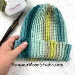 Ribbed, striped crochet hat on a table with a hand holding it, ball of yarn, and crochet hook. Text reads: BananaMoonStudio.com