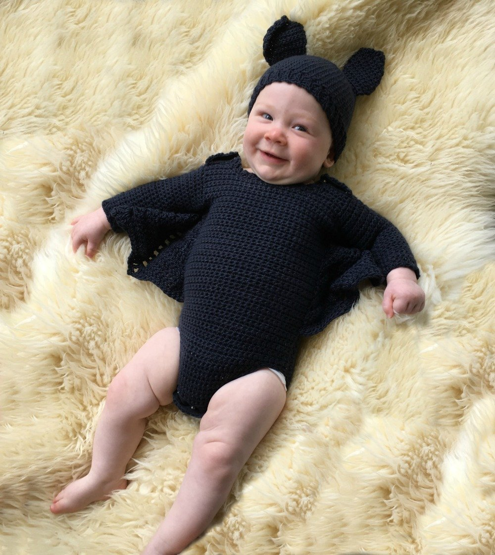 baby in a crochet bat costume with a black hat and bat ears, a black crochet onesie with bat wings between the arms and body.