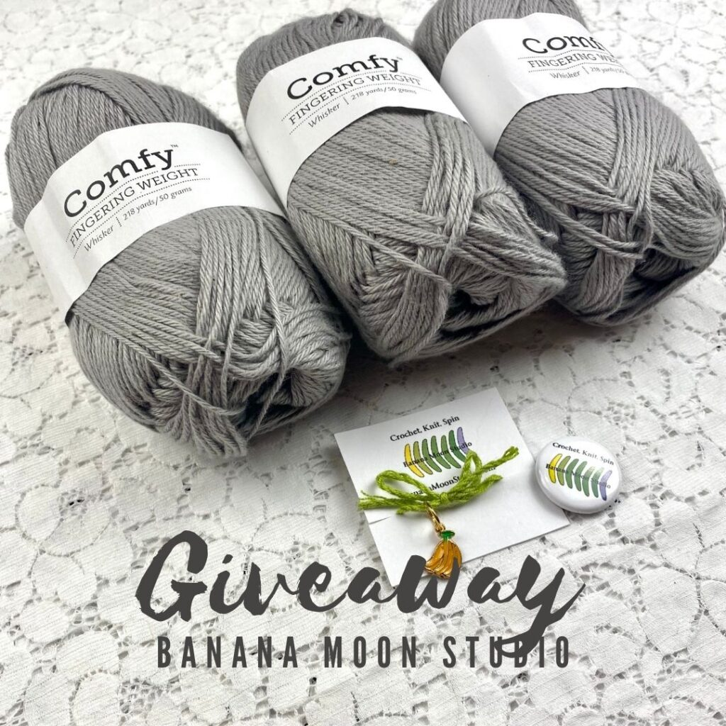 3 skeins of gray We Crochet Comfy Fingering Weight yarn, Banana Moon Studio stitch marker, and Banana Moon Studio button on a white lace background. Text reads: Giveaway. Banana Moon Studio.