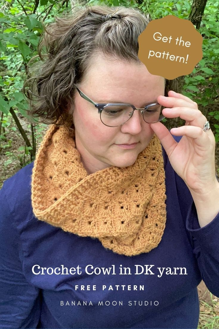 Woman wearing a crochet cowl with a crochet fan stitch pattern and ribbed edges. She is standing in the woods and adjusting her glasses. Text reads: Get the pattern! Crochet Cowl in DK yarn. Free pattern. Banana Moon Studio.