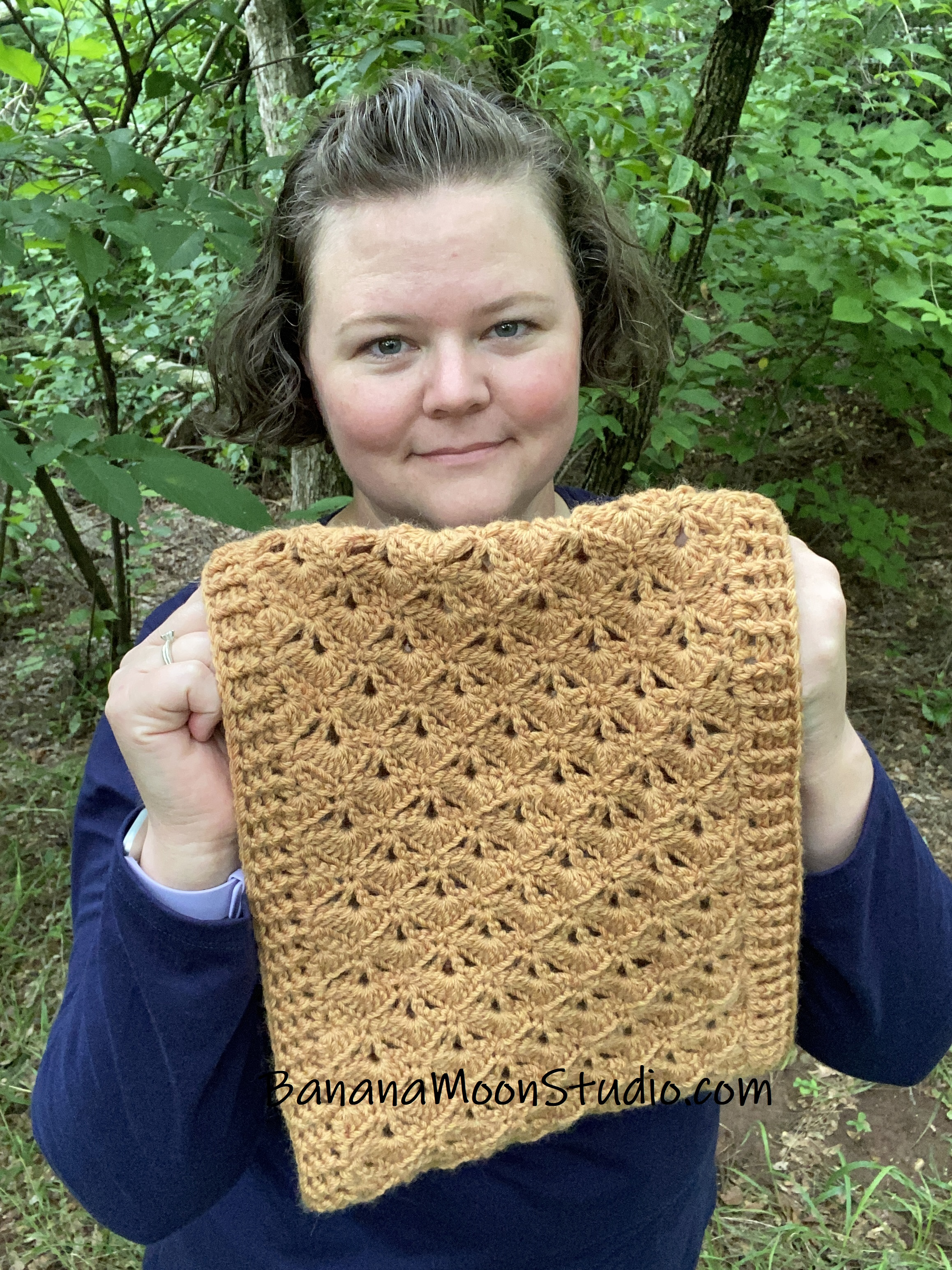 Woman holding up a crochet cowl with a crochet fan stitch pattern and ribbed edges. She is standing in the woods. Text reads: BananaMoonStudio.com.