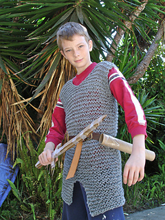 Young teen wearing a red shirt, a knit hauberk that looks much like chainmail, a belt, and scabbard, and holding a toy sword. Palm trees in the background.