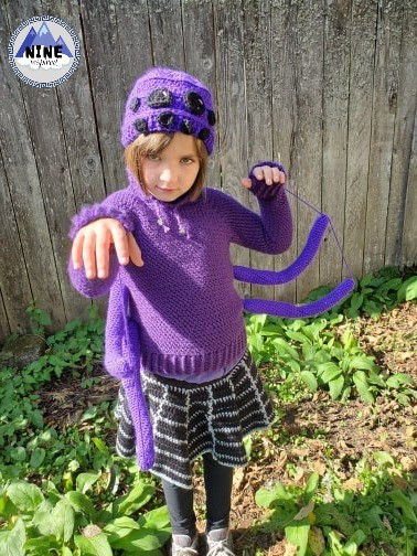 """A child wearing purple hat with black crochet """"spider eyes"""" on it, a purple crochet sweater with crochet """"spider legs"""" also in purple, attached to the sides, and a back skirt with gray lines to look like a spiders web. Wooden fence and green plants in the background. Designer's logo reads: Nine Inspired and has blue mountains on it."""