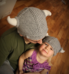 """An adult is wearing a gray Viking style crochet hat with lines and bobbles on it. There is a crochet white """"horn"""" on each side of the hat. The adult is looking down. They are holding a child that is wearing a smaller version of the same crochet hat and the child is looking up at the camera."""