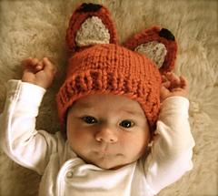 Very young baby laying on a furry background, wearing an orange, knit hat with ears to look like a fox. Baby is wearing a white onesie with long sleeves.