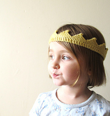 Child wearing a small knit crown that is golden yellow. Off-white background.