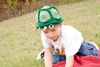 Young child wearing a hat in two shades of green that resembles the shell of a box turtle. There are two round eyeballs on the front as turtle eyes. The child is on the ground, outside.