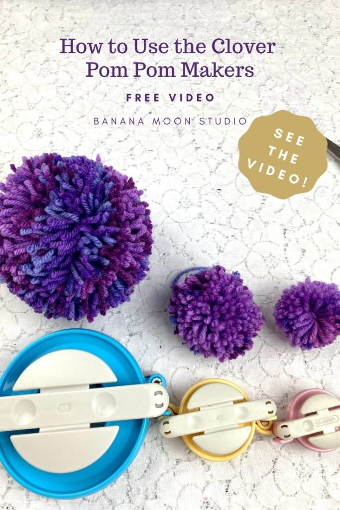Purple pom poms and Clover pom pom makers on a white lace background. Text reads: How to Use the Clover Pom Pom Makers. Free video. Banana Moon Studio. See the video!