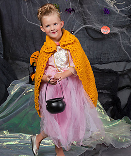"""Young child wearing a pink """"princess"""" dress, ballet flats, and a golden yellow crochet cape with a lacy collar and edging. She is holding a small, plastic cauldron and there is a background of black and iridescent green material and artificial spider webs."""
