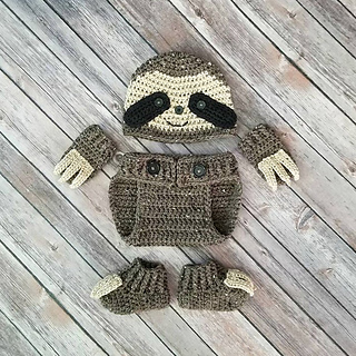 Crochet hat, diaper cover, mitts, and booties to look like a sloth. On a wooden background.