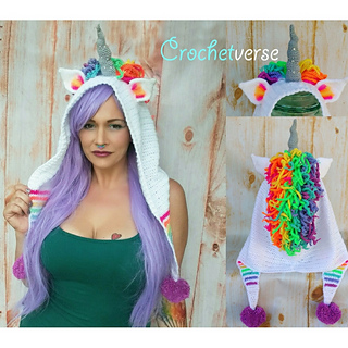 Woman wearing a white and rainbow-colored unicorn hood and emerald green camisole. She has long purple hair. The unicorn hood is mostly white, with rainbow main, silver horn, rainbow stripes, and purple pom poms on the ends.