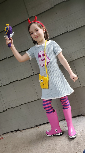 Child dressed in a crochet costume and standing on cement with a wooden shingle wall behind them. The child is wearing a red headband with horns on it, a gray dress with white collar and edgings and a pink octopus applique on it. They are wearing a yellow star shaped purse with a cross-body strap, striped pink and purple tights, and pink rain boots. They are holding up a scepter that is purple and white with a gold star on it.