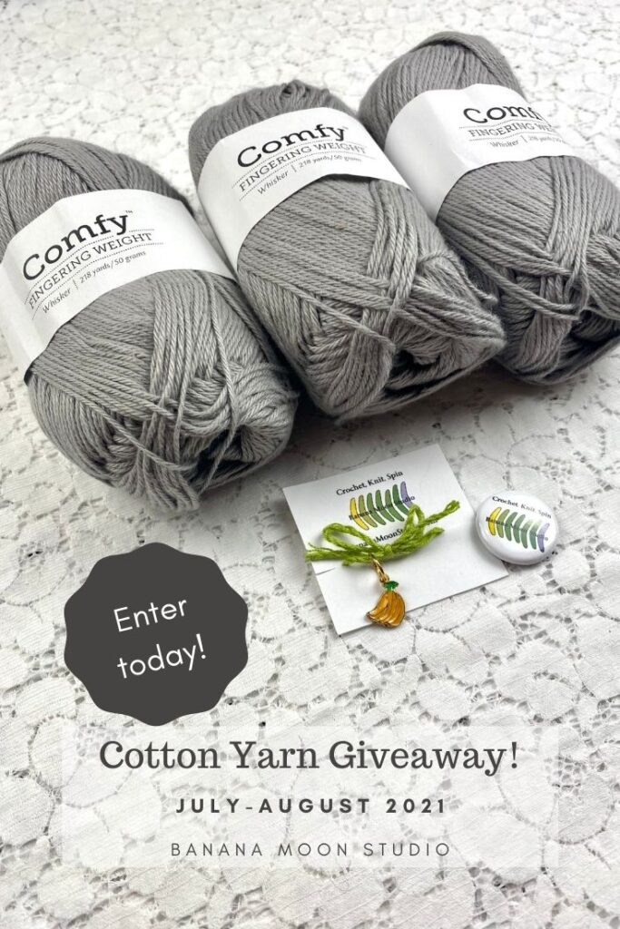 3 skeins of gray yarn from We Crochet, Banana Moon Studio stitch marker, and Banana Moon Studio button on a white lace background. Text reads: Comfy Fingering Weight. Enter today! Cotton Yarn Giveaway! July-August 2021. Banana Moon Studio.