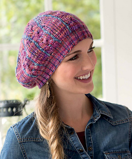 Woman wearing a ribbed colorwork knit beret hat pattern in pink and blue. She is wearing a denim jacket and standing in front of a sunny window.