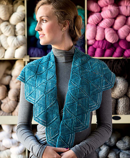 Woman wearing a double-sided knit shawl  that is blue. She is also wearing a gray long-sleeved t-shirt. There are shelves full of yarn in the background.