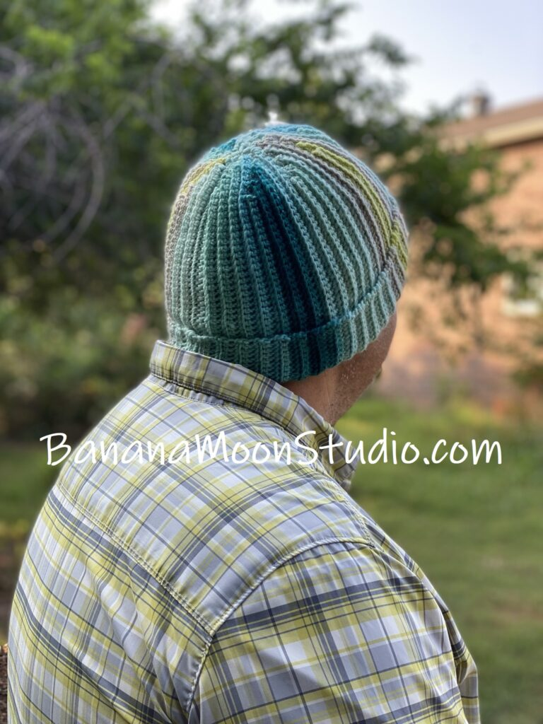 Man wearing a teal striped crochet hat with folded brim. Text reads: BananaMoonStudio.com.