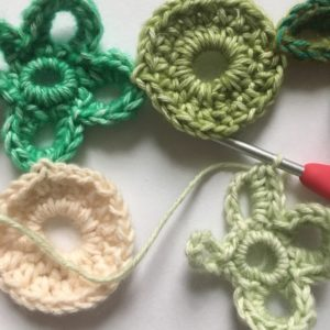 Small crochet motifs in various shades of green and pale pink. Some are shaped liked O's and some like X's. They are in the process of being joined together as the last is crocheted.
