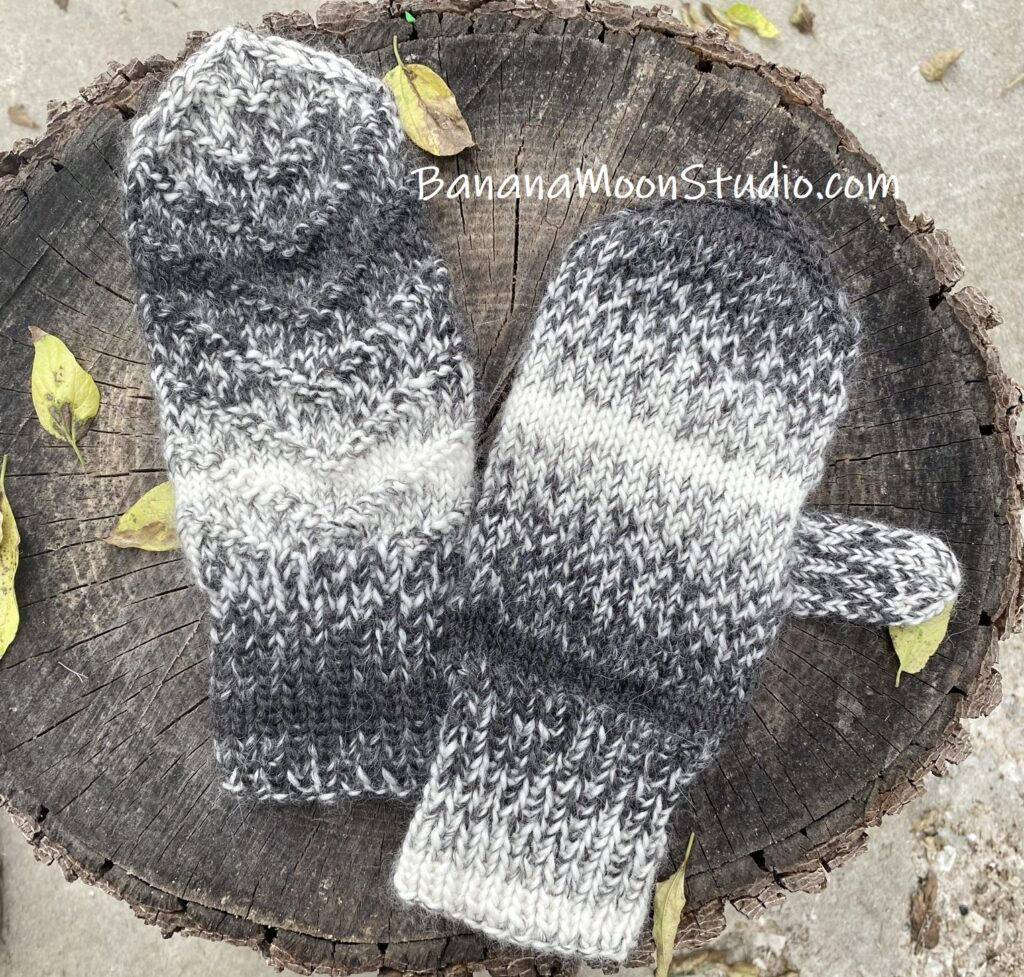 Black and white handknit mittens on a log with yellow leaves in the background.