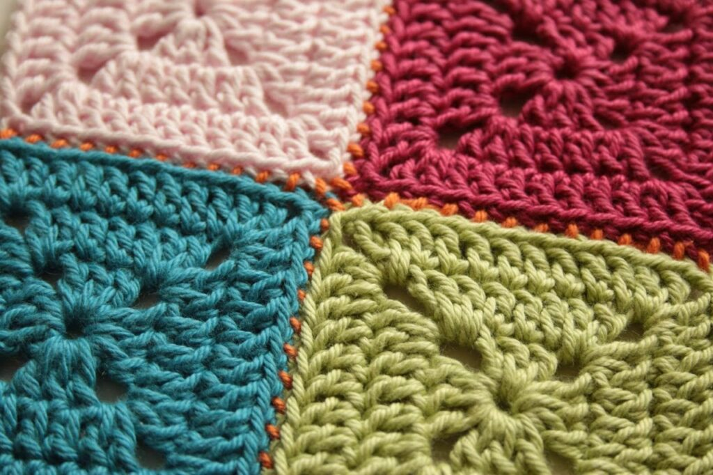Four crochet granny squares, one pink, one red, one teal, one green, seamed with orange yarn.