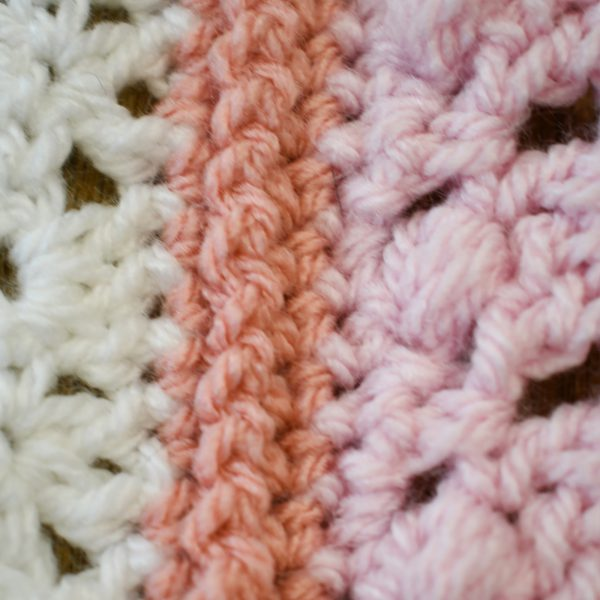 A close-up of a white crochet motif and a pink crochet motif, joined with a raised coral-colored seam.
